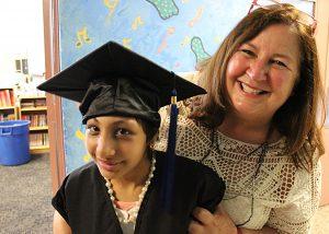 A student wearing a graduation cap stands next to a teacher