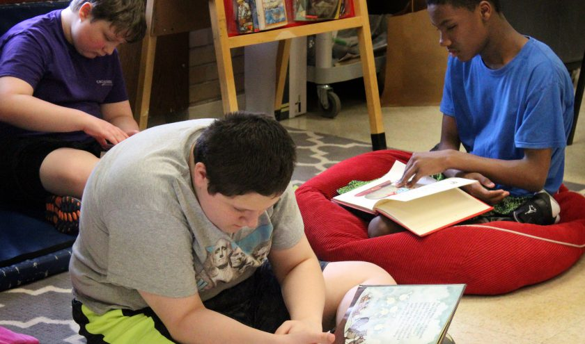 Three students sit on beanbags while reading books.
