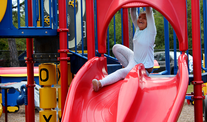 A smiling student plays on a colorful playground slide.