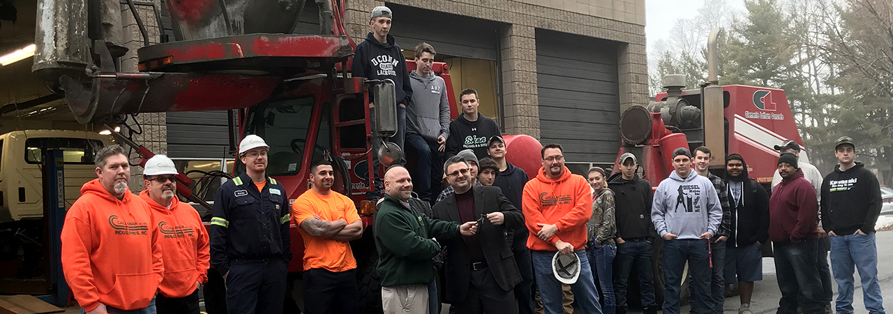 Representatives from Albany-based Callanan Industries stand with a group of Diesel Technology students in front of a cement truck.