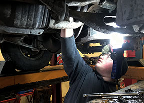 A bright light shines on a student working on the underside of a vehicle that is on a lift.