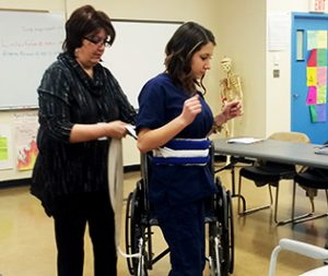 Teacher helping a person in a wheelchair to stand up using a waist support.