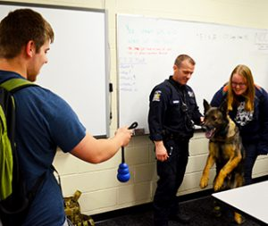 Student and police officers interacting with a police dog.