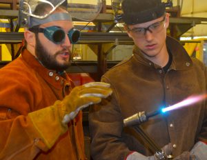 Teacher Don Mattoon wears goggles and headgear while instructing a welding student