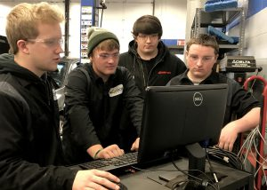 Four automotive students stand together and study information on the screen of a computer.