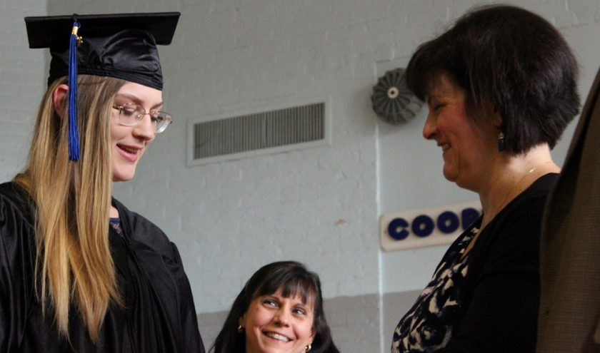 Two smiling teachers hand a student wearing a graduation cap and gown her diploma.