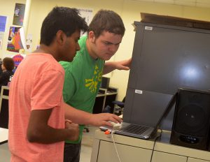 Two Internet App students look at a laptop computer as they work to design a website.