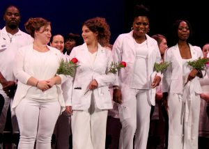 CTE Adult Nursing students stand arm-in-arm at their June 26 graduation ceremony.