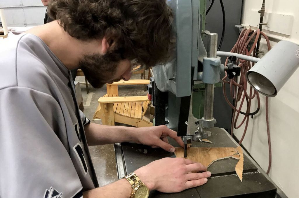 Student with head bent cuts a piece of wood with electric jigsaw.
