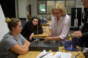 Students and a teacher gather around a machine used to make precise measurements needed when making metal parts.