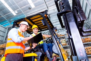 A fork lift driver and job foreman in a warehouse review a checklist.