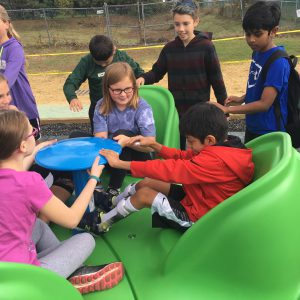 A group of students play together on a piece of accessible playground equipment.