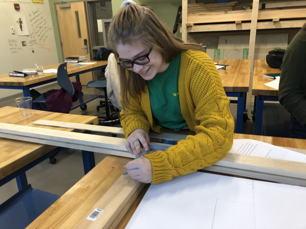 Teenage girl works on blueprints at a Center for Advanced Technology.