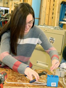 Career and Technical School student Quinn Rickard cuts wires with a hand-held tool.