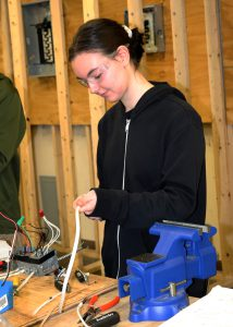 Career and Technical School student Sydney Rickard holds wires in her hand.