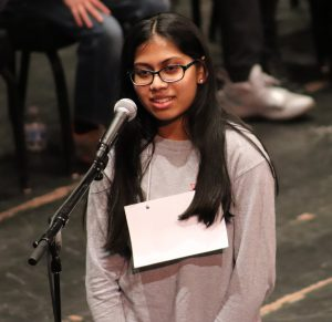 A middle school girl spells a word into a microphone during the Regional Spelling Bee at Proctors Theatre.