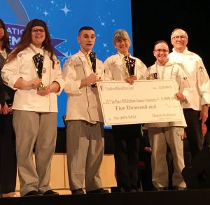 Career and Technical School Culinary students and their teachers pose with a large scholarship check.