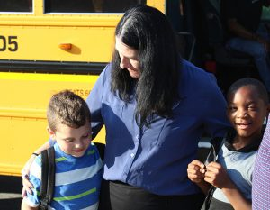 Teacher greeting two students as they arrive to school with school bus in the background