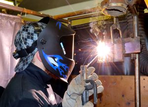 Capital Region BOCES Adult Welding and Metal Fabrication student Tom Resso wears a welding helmit as he works with a mig gun.