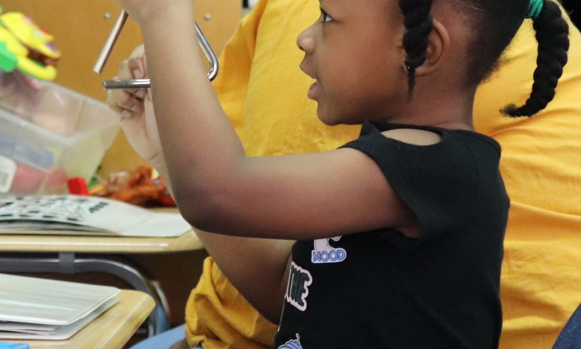 A young girl seated at her desk rings a triangle during a math lesson.