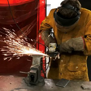 Sparks fly as welding student Donald Ploof, wearing protective gear, works in a Career and Technical School classroom.