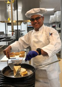 Culinary student Angelo Carino, wearing a chef's uniform, smiles for the camera as he prepares a grilled cheese sandwich.