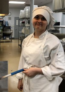 Culinary student Ginger Crandall, wearing a white chef's uniform, smiles for the camera while she cooks.