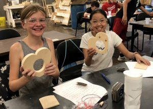 Two smiling girls wearing protective goggles display the wooden hearts they made during the BOCES Career and Techincal School summer camp.