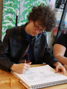 Capital Region BOCES graduate Tyler Blackman, wearing a black leather jacket and sitting before green and white backdrop, sketches scenery in a notebook.