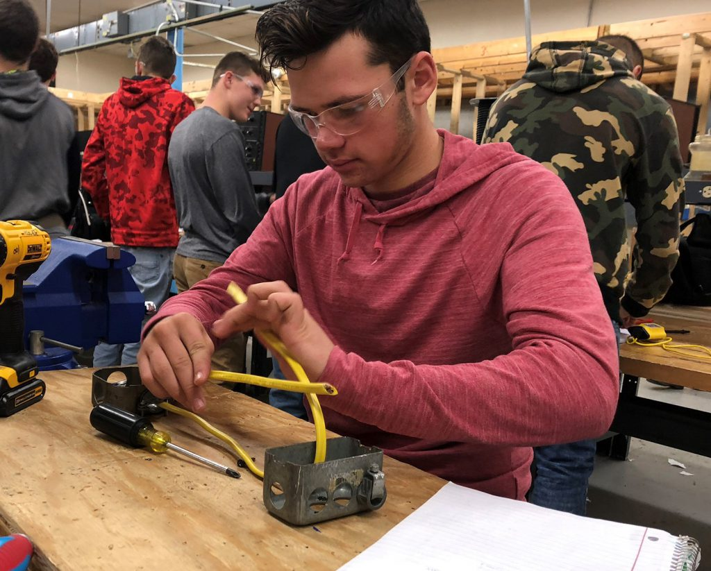 A student wearing a red hoodie and protective eye wear works with wires in a Capital Region BOCES electrical trades classroom.