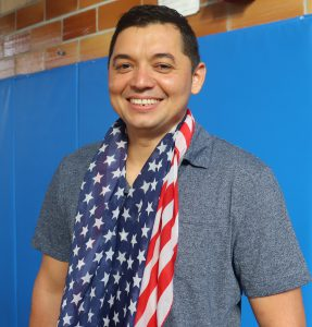 Adult Education student Javier Villatoro, wearing a blue short sleeved polo and an American flag scarf, smiles for the camera.