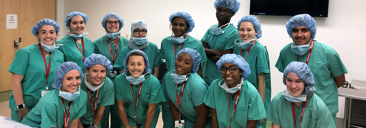 Smiling group portrait of students wearing operating room scrubs
