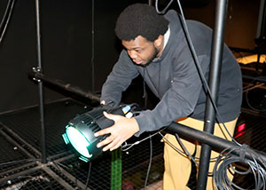 A student in the Entertainment Technology program adjusts a spotlight.