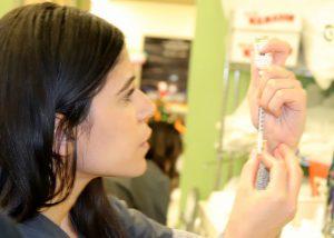 Adult Nursing student fills a syringe.