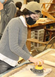 Student Cora Tribunella, wearing a tan cap, protective eyewear and a face mask, uses an orbital sander to to smooth a piece of wood in a Capital Region BOCES Building Trades classroom.