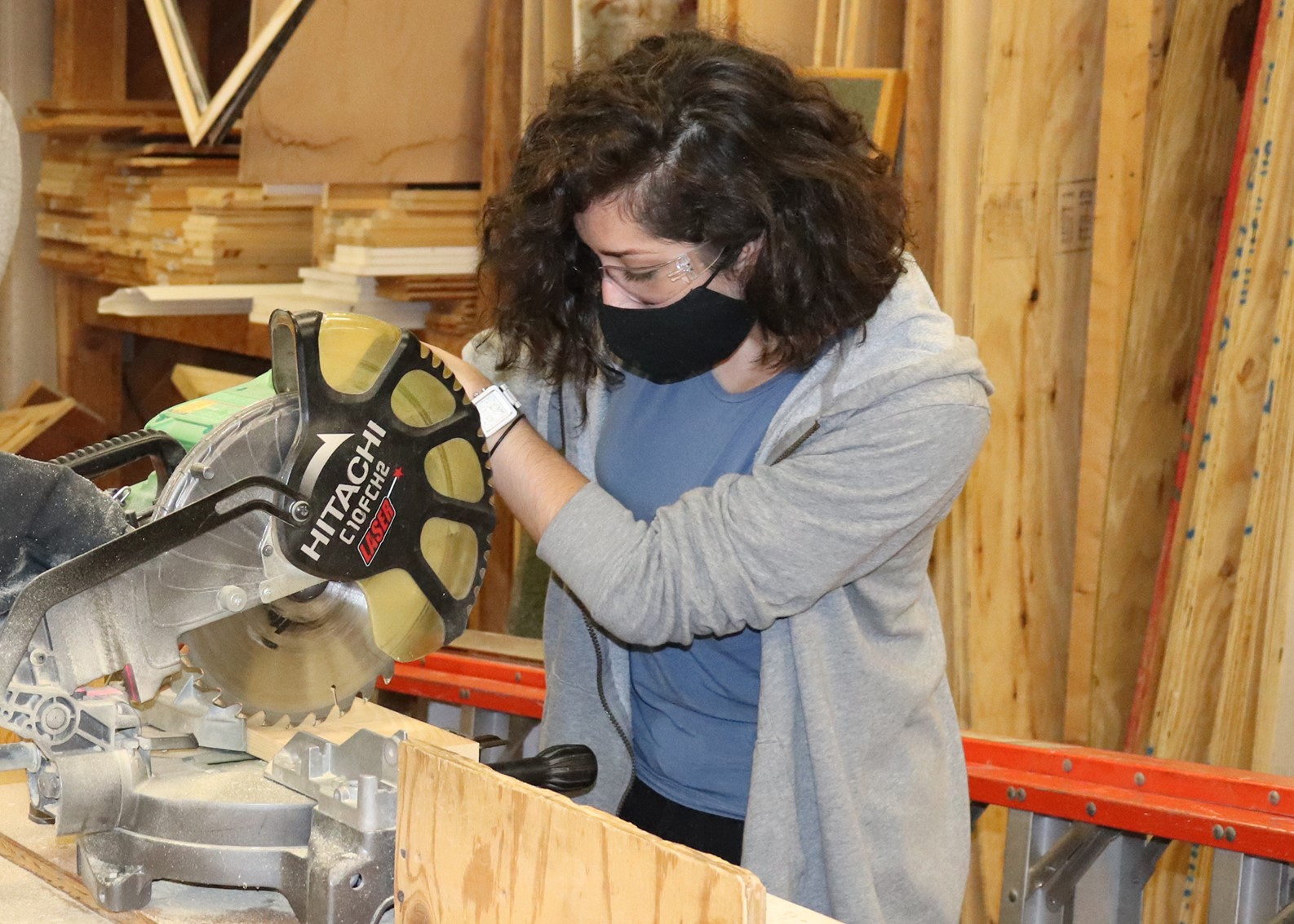 Student Isabel Tribunella. wearing protective eyewear and a face mask, uses a miter saw to cut through a board in a Capital Region BOCES Building Trades classroom.