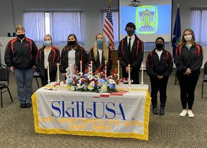 Five Albany Career and Technical School Skills USA officers, wearing their blue and red uniform, stand in a row behind a table draped in a SkillsUSA banner and holding flowers and candles.