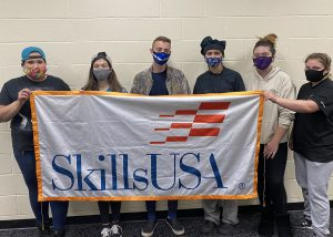 Six Schoharie Career and Technical School Skills USA officers, holding a SkillsUSA banner and wearing protective face masks, stand in a row along a beige wall.