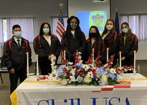 Six Albany Career and Technical School Skills USA officers, wearing their blue and red uniform, stand in a row behind a table draped in a SkillsUSA banner and holding flowers and candles.