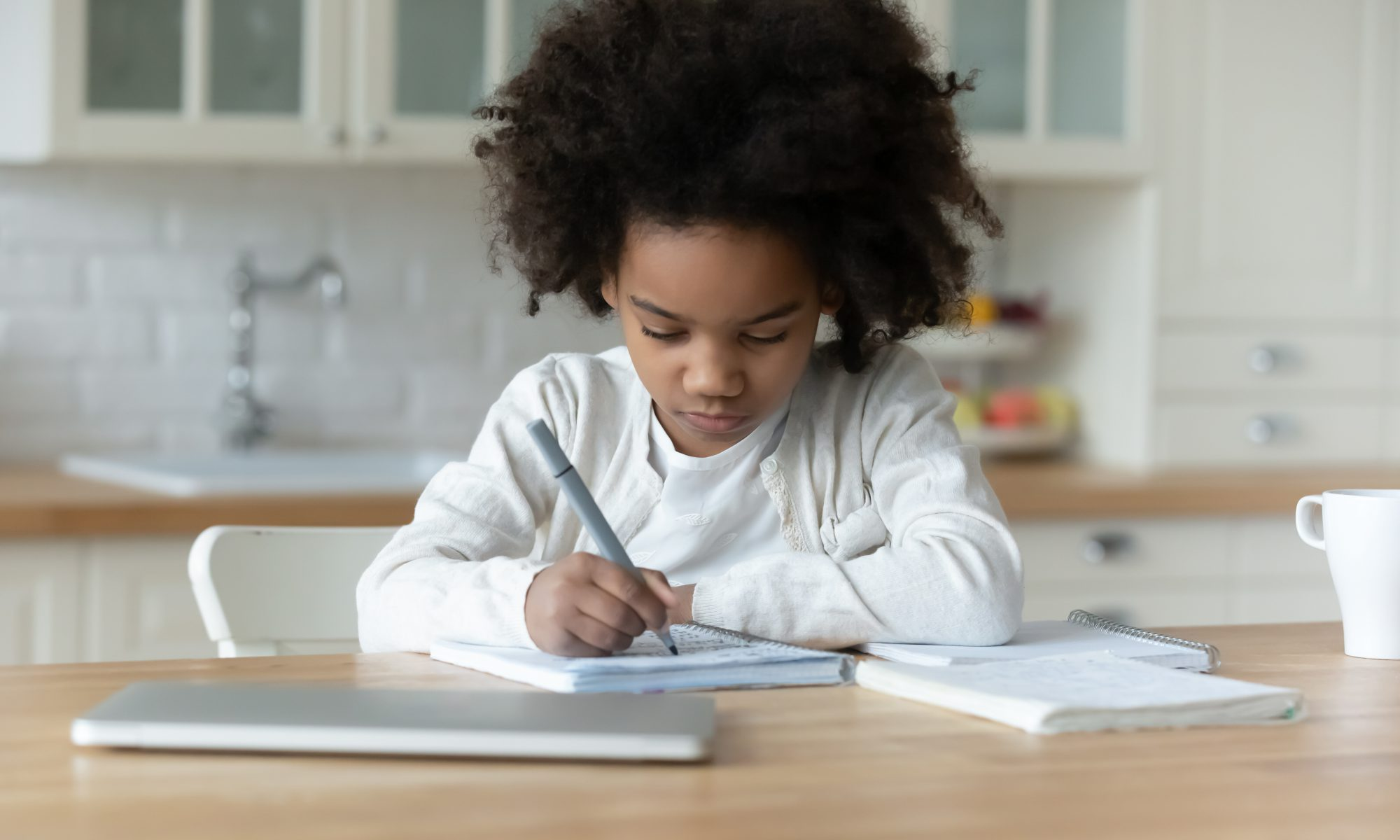 A young girl wearing a white t-shirt and cardigan sweater and holding a pen, sits at a kitchen table and writes in a spiral-bound notebook.