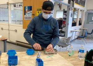 An adult student wearing a black ball cap turned backwards, glasses and a face mask works with wiring at a workbench in an Electrical Trades classroom.
