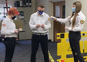 Three students, wearing security uniforms and protective face masks, learn to collect crime scene evidence in a Capital Region BOCES Criminal Justice classroom.
