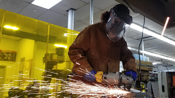 Adult Welding and Metal Fabrication student Laura Kessler, wearing a face mask and heat protective clothing and a shield welds metal as sparks fly in a Capital Region BOCES classroom.