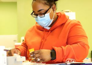 Adult Nursing student Sonisha Robinson, wearing eyeglasses, a light blue face mask and orange hooded sweatshirt, measures medicine in a Capital Region BOCES classroom.
