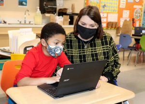 A Capital Region BOCES student wearing a bright red sweatshirt and protective face covering, and a teacher wearing a black and yellow plaid sweater and face covering, sit together at work on a Chromebook.