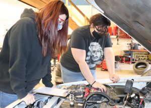 Auto Trades Technology students Makaya King, who has long auburn hair and is wearing a protective eyeglasses, an American flag printed face mask and a black hoodie, and Destiny Honsinger, with hair pulled back and wearing protective eye glasses, a black face mask and Marilyn Monroe skull t-shirt, inspect the engine of a car in a Capital Region BOCES auto lab.