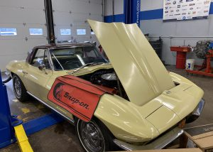A yellow 1967 Corvette with its hood raised is parked in a bay of a garage at the Capital Region BOCES Career & Technical School.