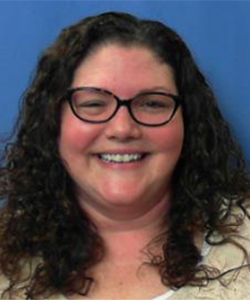 Capital Region BOCES Administrative Aide Linda Stapleton, who has long brown curly hair and is wearing a light yellow top and tortoise-framed eyeglasses, smiles for the camera. Linda is Capital Region BOCES' March 2021 commitment award recipient for improvement.