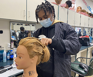 A high-school age student, who has dark brown braids and is wearing a black protective jacket and light blue face mask, styles the hair of a manequin in a Capital Region BOCES Cosmetology classroom.