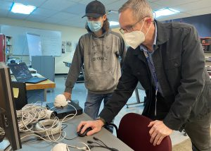 A student, wearing a black ball cap, blue protective face mask and grey sweatshirt, and a teacher, with short hair, eyeglasses and a white face mask, work together at a desktop computer in a Network Cabling classroom. White electrical cables lay on the table where they are working.